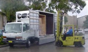 Staff carefully loading a container full of packed boxes at your home or office with a forklift