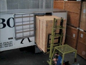 Forklift placing a cubic metre box inside our furniture removal truck by a staff member